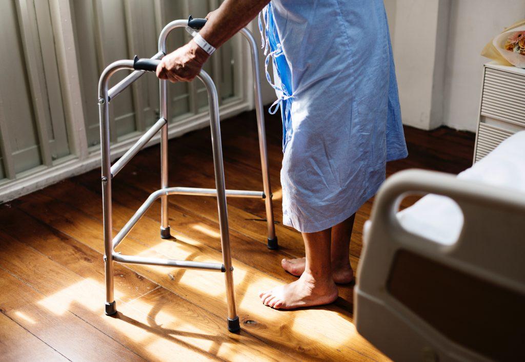 Personne âgée qui marche avec un déambulateur.