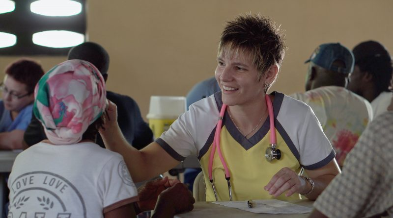 Une aide-soignante qui sourie à une jeune patiente.