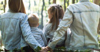 Famille de dos assise dans une forêt
