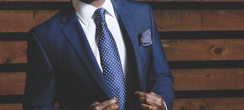 zoom sur le buste d'un homme qui porte un costume bleu marine avec une chemise blanche et une cravate bleu marine