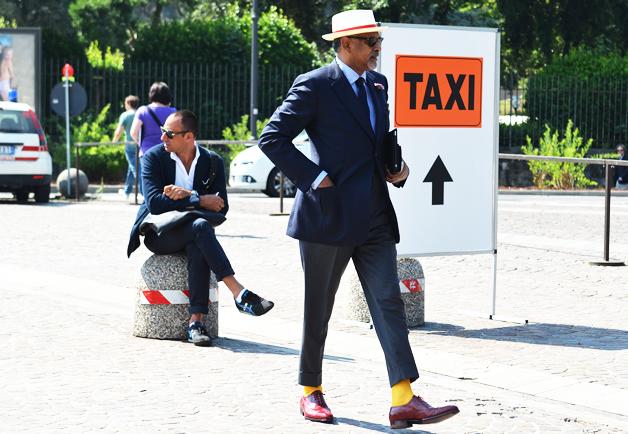 homme portant une veste de costume bleu marine un pantalon gris des chaussettes jaunes des chaussures marron et un chapeau blanc et rouge