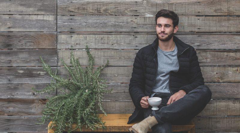 homme brun assis sur un banc portant un jean un t shirt gris une doudoune foncée et des boots beige une tasse à la main