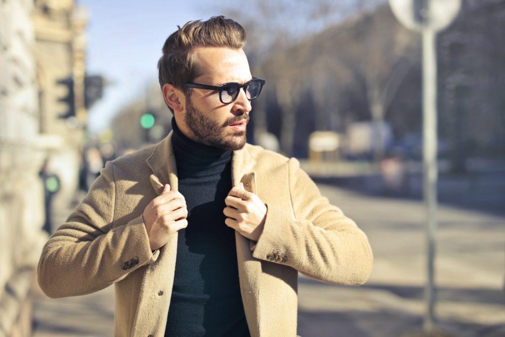 homme avec des lunettes portant un pull à col roulé noir et un manteau beige