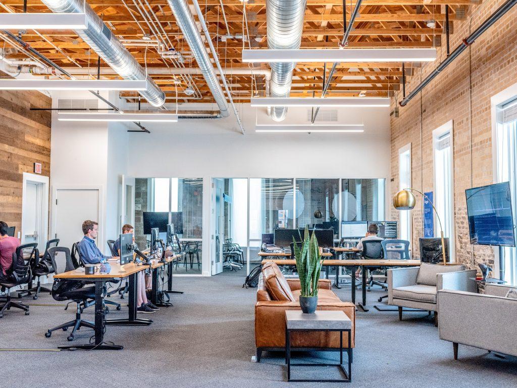 open space d'entreprise décoré style industriel avec bureaux en bois canapé et plante