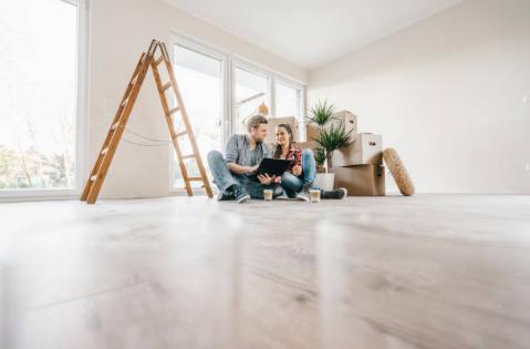 deux personnes assises par terre dans un logement vide avec cartons échelle et plantes